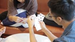 asian chinese roommates having fun playing poker at home