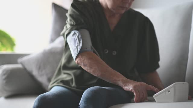 asian chinese senior adult woman checking blood pressure monitoring - measuring stock videos & royalty-free footage