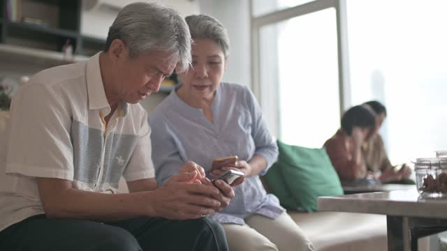 asian chinese senior couple with presbyopia having difficulty  trying to learn using smart phone at living room during weekend leisure time - struggle stock videos & royalty-free footage
