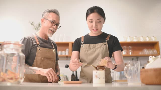 asian chinese senior male barista teaching his daughter making coffee at cafe bar counter - part of stock videos & royalty-free footage