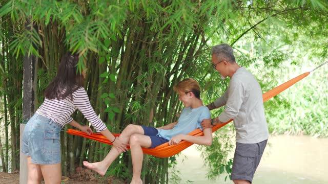 stockvideo's en b-roll-footage met aziatische chinese hogere mens en dochter die zijn zoon helpen die bij hangmat bij rivieroever onder bamboebomen liggen - achterover leunen