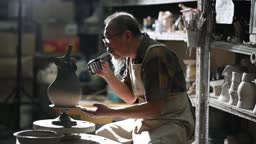 Asian chinese senior man clay artist blowing paint on the sculptor working in his studio with spinning pottery wheel