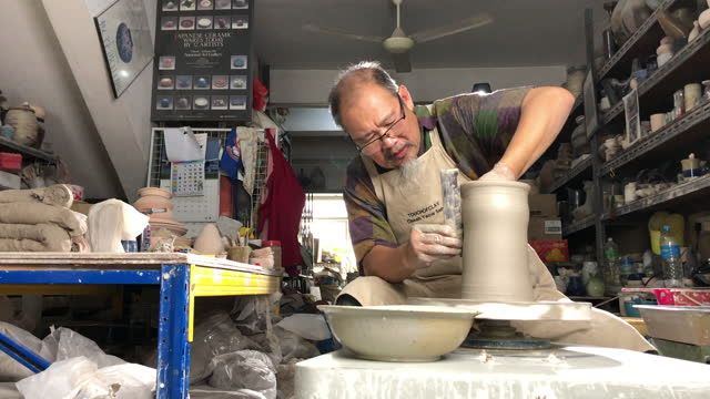 asian chinese senior man clay artist making pottery on a spinning pottery wheel in his craft studio - pottery stock videos & royalty-free footage
