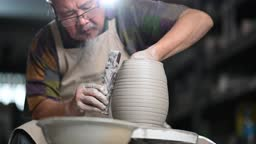 Asian chinese senior man clay artist working in his studio with spinning pottery wheel