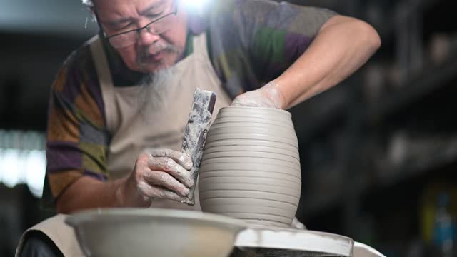 asian chinese senior man clay artist working in his studio with spinning pottery wheel - art and craft stock videos & royalty-free footage