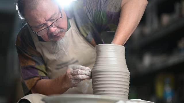 vidéos et rushes de artiste chinois asiatique d'argile d'homme aîné travaillant dans son atelier avec la roue de poterie de filature - céramique