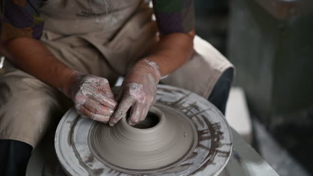 asian chinese senior man clay artist working in his studio with spinning pottery wheel - working seniors stock videos & royalty-free footage