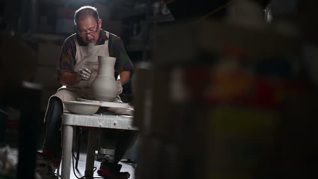 asian chinese senior man clay artist working in his studio with spinning pottery whee - pottery stock videos & royalty-free footage