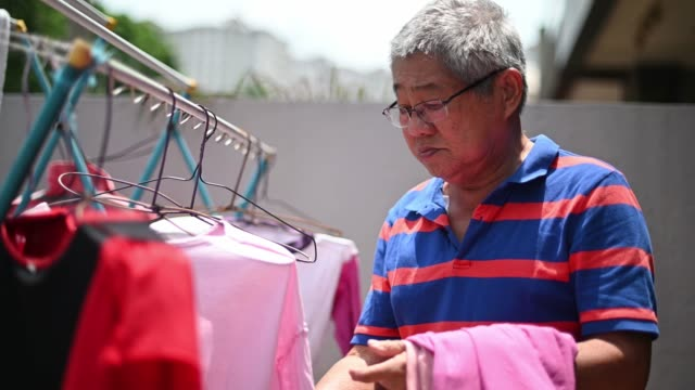 asian chinese senior man collecting clothes hanged at front yard after cleaning - chores stock videos & royalty-free footage