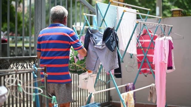 服を集めるアジアの中国人先輩男性は、掃除後に前庭で絞首刑にされた - 物干し点の映像素材/bロール