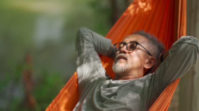 asian chinese senior man enjoying his afternoon lying down at hammock at riverside under bamboo trees - lying on back stock videos & royalty-free footage