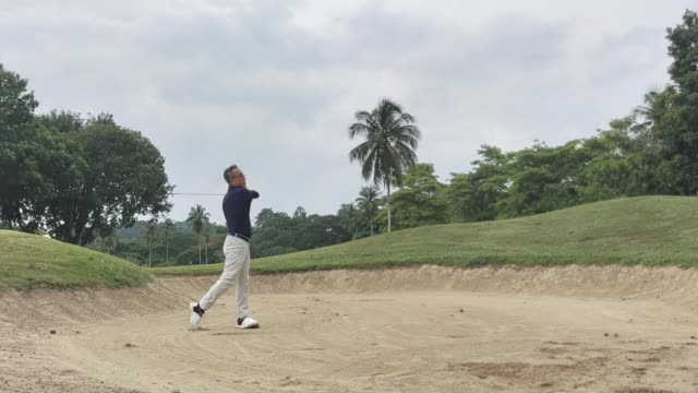 asian chinese senior man golfer hitting his golf ball in a sand trap with his iron club - senior golf swing stock videos & royalty-free footage