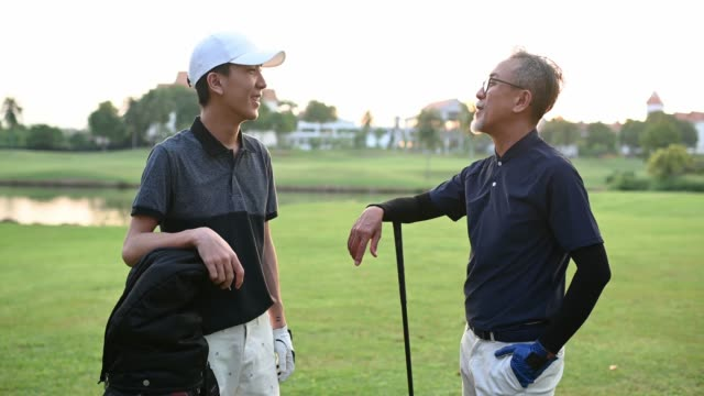 asian chinese senior man golfer talking to his son at the end of the game happily in melaka golf course - tee stock videos & royalty-free footage