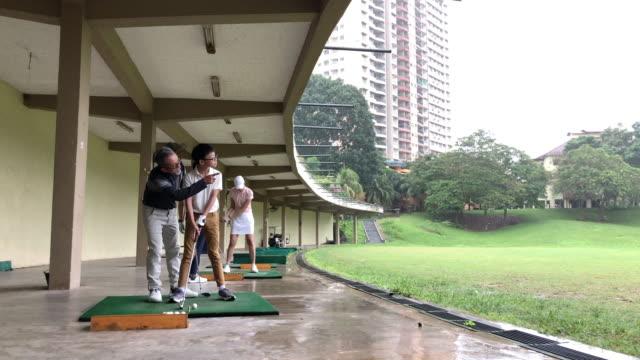 asian chinese senior man golfer teaching his son playing golf at golf driving range - driving range stock videos & royalty-free footage