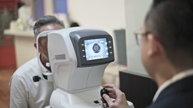 asian chinese senior man having an eye exam at ophthalmologist's office - lens optical instrument stock videos & royalty-free footage