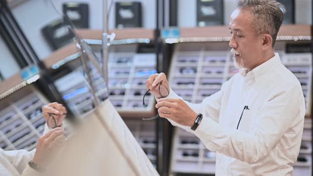 vídeos y material grabado en eventos de stock de hombre mayor chino asiático probando anteojos frente al espejo en la tienda de óptica - un solo hombre maduro