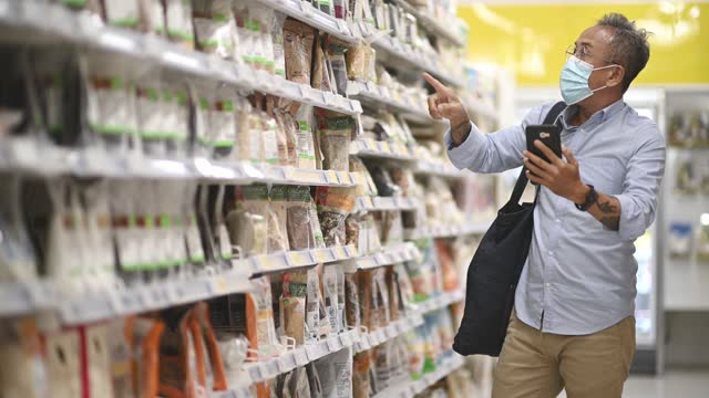 asian chinese senior man videocall and shopping in supermarket looking for dairy product - genderblend stock videos & royalty-free footage