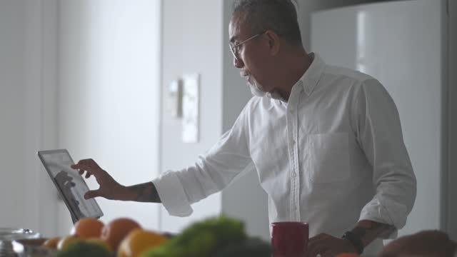 asian chinese senior man with beard gray hair using digital tablet while enjoying his morning coffee at kitchen counter - mature men stock videos & royalty-free footage