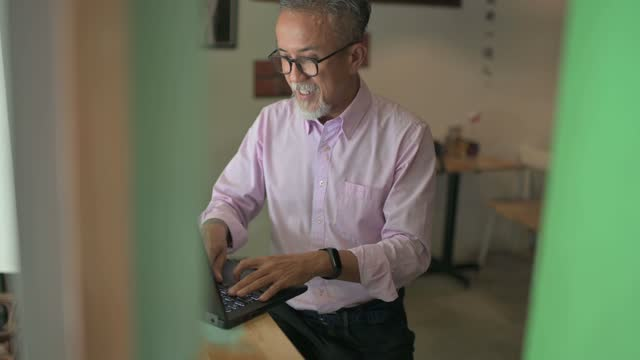 asiatische chinesische senior mit bart arbeiten mit laptop im café - chinesischer abstammung stock-videos und b-roll-filmmaterial