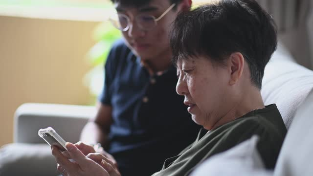 asian chinese senior woman looking on her phone checking for message social media surf the net - malaysia stock videos & royalty-free footage