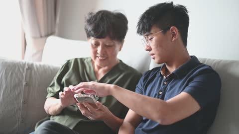 vídeos y material grabado en eventos de stock de asiática mujer mayor china mirando en su teléfono buscando mensaje de las redes sociales navegar por la red - vida sencilla