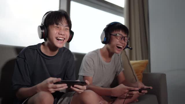 vidéos et rushes de 2 frère chinois asiatique de frère s'asseyant sur le sofa jouant le jeu vidéo dans le salon - frère