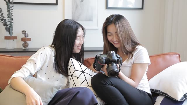 asian chinese sisters checking photos form their camera at home - digital camera stock videos & royalty-free footage
