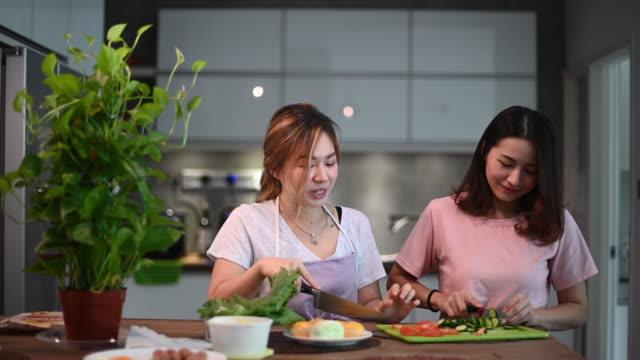 vidéos et rushes de 2 soeurs chinoises asiatiques ayant le temps de liaison ensemble dans la salle à manger préparant la nourriture de petit déjeuner heureux parlant - soeur