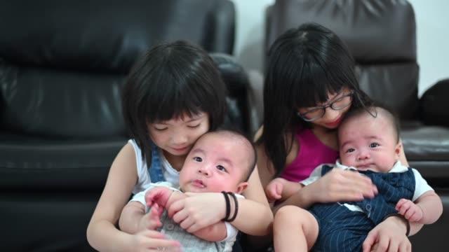 vidéos et rushes de soeurs chinoises asiatiques prenant soin de leur frère jumeau de bébé au salon - famille avec quatre enfants