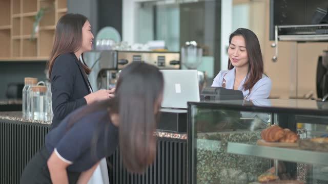 stockvideo's en b-roll-footage met de aziatische chinese kleine bedrijfseigenaar overhandigt het dessert aan haar klant bij keukenteller het glimlachen - klanten georiënteerd