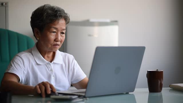 asian chinese smiling mature businesswoman working on laptop in her office - tjänstekvinna bildbanksvideor och videomaterial från bakom kulisserna
