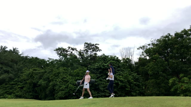 asian chinese smiling young couple golfer family bonding and walking on the golf course - golf bag stock videos & royalty-free footage