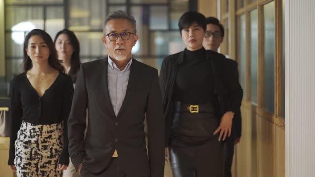 vídeos y material grabado en eventos de stock de asiático chino exitoso equipo de administración de la oficina caminando hacia la actitud fresca de la cámara - distante
