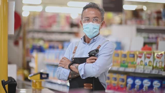 vídeos de stock, filmes e b-roll de asiático chinês supermercado pequeno empresário homem sênior de pé cruzou sorrindo para a câmera - profissão na área de serviços