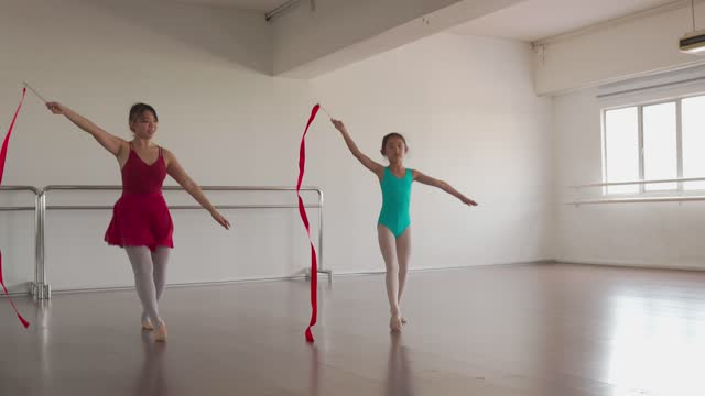 asian chinese teenag girl practicing rhythmic gymnastics with colored ribbon with her elementary student at gymnastics school. ballet school. - human limb stock videos & royalty-free footage