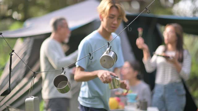asian chinese teenage boy picking up hanging metal mug at camping tent for coffee drink - coffee drink stock videos & royalty-free footage