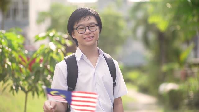 asian chinese teenager boy with school uniform waving national flag in public park - one teenage boy only stock videos & royalty-free footage