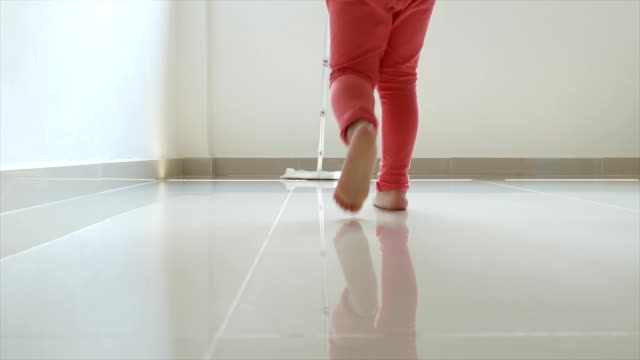 Asian chinese toddler give a helping hand in cleaning the floor