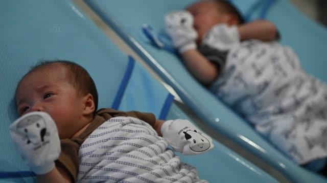 ベッドの寝ている2アジアの中国の双子の赤ちゃん - そっくりさん点の映像素材/bロール