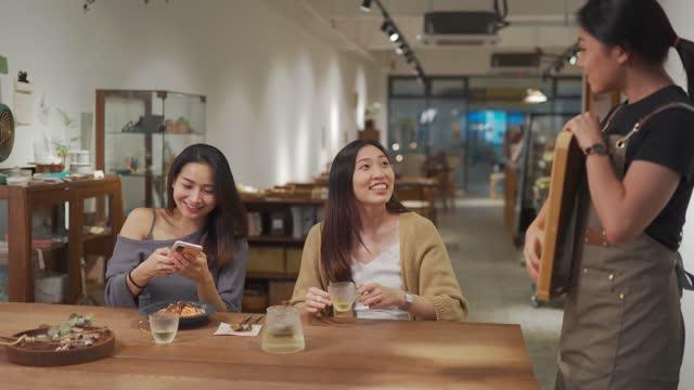 vídeos de stock, filmes e b-roll de garçonete chinesa asiática assumiu a comida na bandeja do balcão de cozinha servindo para suas 2 clientes do sexo feminino no restaurante - smart