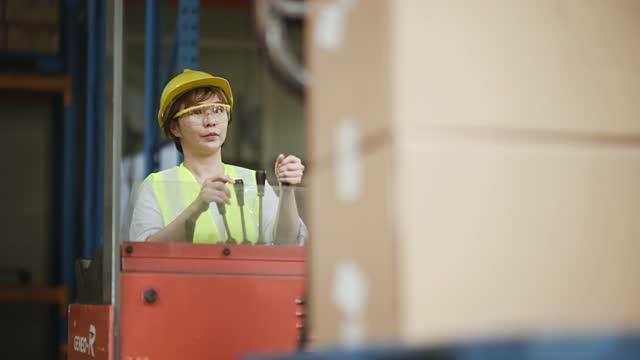 asiatische chinesische Lagerarbeiterin, die Gabelstapler in Industriefabrik betreibt