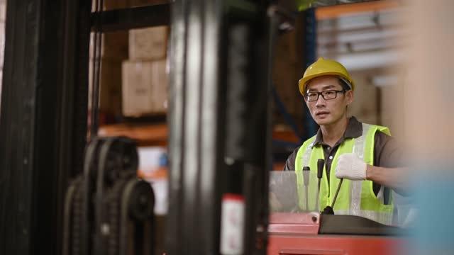 asiatische chinesische Lager männlich Arbeiter betrieb Gabelstapler arbeiten in Industriefabrik