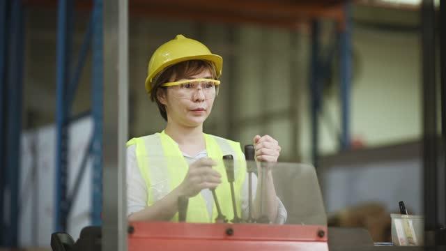 asiatische chinesische Lager mid erwachsene Frau mit Hardhat und Schutzbrille am Gabelstapler Schreiben Aktualisierung Dokument arbeiten in Industriefabrik