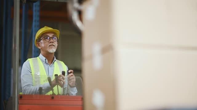 asiatische chinesische Lager Senior Arbeiter bei Gabelstapler zählen Lager in Industriefabrik arbeiten