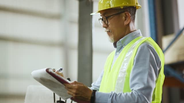 asiatische chinesische Lager Senior Arbeiter bei Gabelstapler Schreiben Aktualisierung Dokument arbeiten in Der IndustrieFabrik