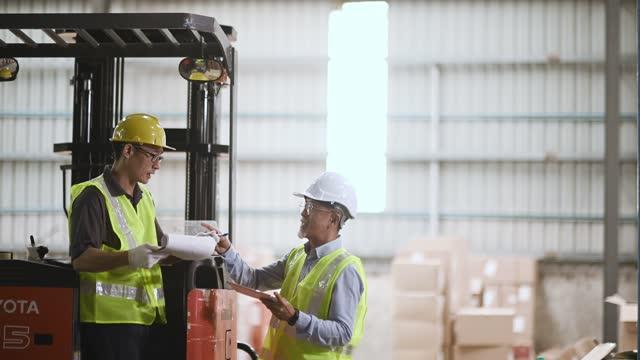 asiatische chinesische Lagerleiter Unterzeichnung Dokumente Empfang Von seinem Kollegen Arbeiter Arbeiter Arbeiten Gabelstapler arbeiten in Industriefabrik