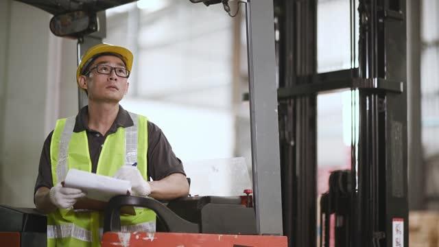 asiatische chinesische Lagerarbeiter bei Gabelstapler zählen Lagerbestand in Industriefabrik arbeiten