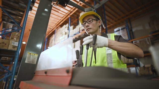 asiatische chinesische Lagerarbeiter betreiben Gabelstapler arbeiten in DerIndustrie Fabrik