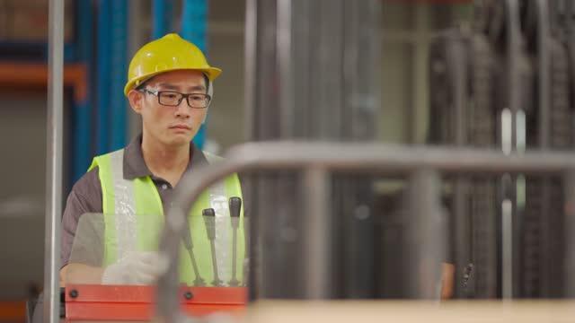 Asiatische chinesische Lagerarbeiter in Betrieb Gabelstapler arbeiten in Industriefabrik