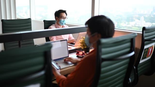 stockvideo's en b-roll-footage met aziatische chinese witte boorden werknemer weer aan het werk na quarantaine met nieuwe sop en sociale distantiëren van ziekte preventie veiligheidsmaatregelen - heropening